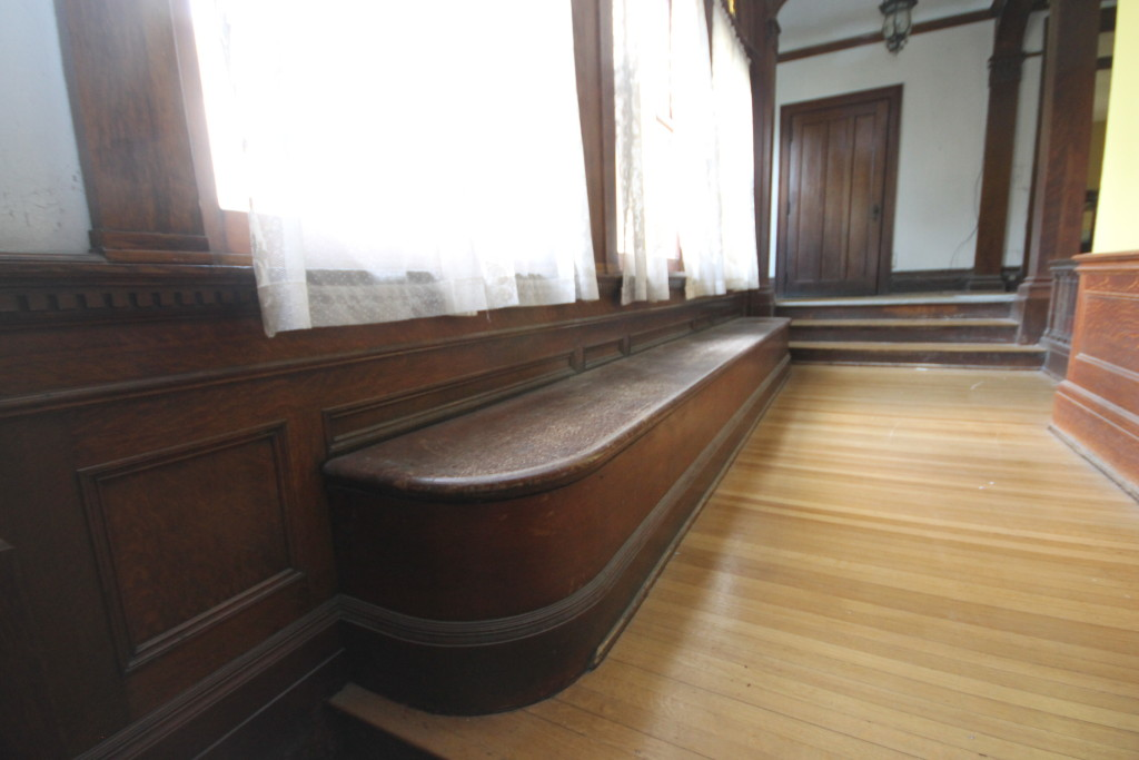 Built in bench below stained glass windows in hall